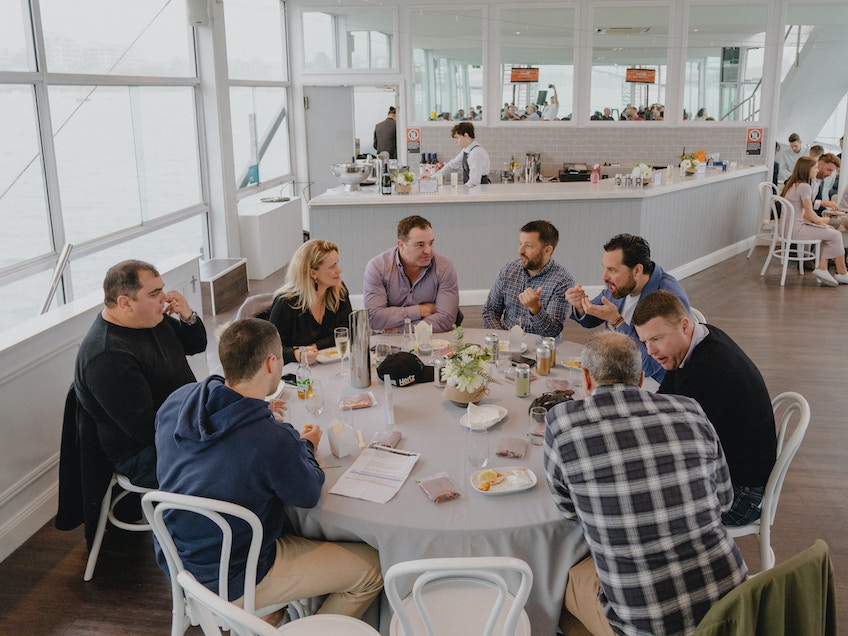 Group of men and women around table at an event at Starship Aqua on Sydney Harbour